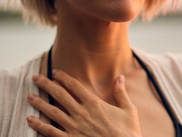 A woman holding her hand on her chest